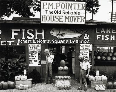 two young men standing outside a market stand, each holding a large melon; signs, including painted fish on sign above doorway