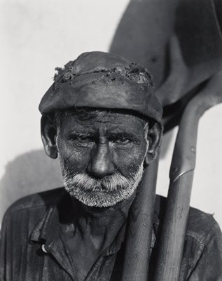 portrait of dark-skinned man with white beard and moustache, wearing a cap with holes and holding two shovels over his PL shoulder