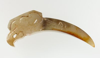 pick or knot opener with incision and relief. White translucent jade with marble brown striation; the side of the moon-curved opener is incised with curvilinear lines (not quite identical at both sides) in capturing the comma or lei-wen design; a rectilinear plaque with relief of a deer is placed at the top; the object ends in curved form as part of the incised curvilinear design. Traces of earth.