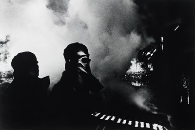 two figures at L: one completely in silhouette, one wearing mask and goggles; clouds of smoke in background; light areas at R