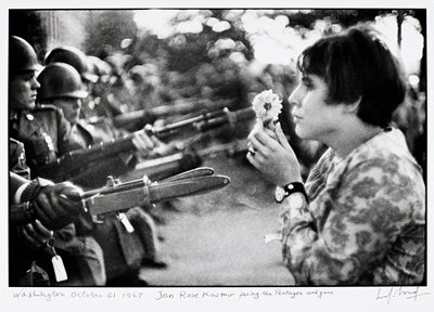 short-haired woman at R holding a flower and facing a row of soldiers holding guns with bayonets