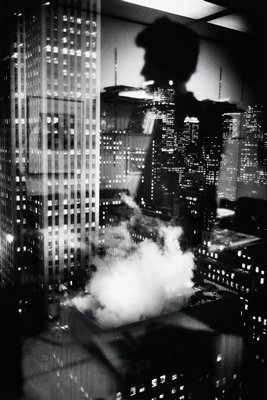 lights in windows of city skyscrapers; smoke coming from roof at bottom center; reflected silhouette at top center