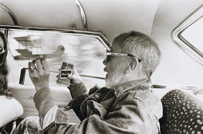 man in profile in back seat of car, wearing large sunglasses and a denim jacket, holding a model plane in his PL hand and a can of beer in his PR hand