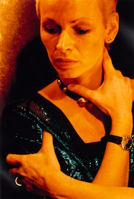bust of woman; arms crossed with hand at neck and shoulder; wearing watch, studded choker and blue shimmer dress