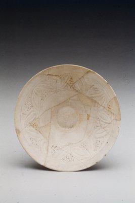 Bowl, carved, and pierced design on white ground under transparent glaze.