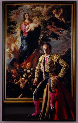 matador seated on a stool covered with a tan cloth, wearing a black and gold costume with coral-colored tie and stockings, holding his red and black sword in his PR hand and his red cape in his PL hand; painting of Mary holding baby Jesus surrounded by cherubs behind man
