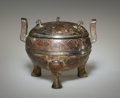 Typical features of the advanced Huai style are displayed in this vessel; one of the foremost treasures of Chinese bronze art. The bowl and d lid form a spherical shape. The slight broadening of the body, together with the short, bulbous legs that barely raise it from the ground, give it an amusingly pompous air. The bent ears are big and heavy, contrasting strongly with the slender animals resting on the lid, their heads turned outward and their legs folded under in the style common in Middle Chou and Huai style bronzes. The decor is effected through silver inlay in a variety of patterns large heart-shaped figures on the lower body; geometricized derivatives of crossing dragons in the neck belt; and designs of bird origin on the sides of the handles. The heart shape appears again on the lid in every second angle of the hexagonal motif. Outside of he angles is a motif probably derived from antithetical pairs of bird dragons. These figures are flanked by large, sinuous dragons. An interesting and historically significant feature is the pear-shaped motif on the bodies of the recumbent animals. they reveal the influence of Ordos art (Northern animal style). See BMFEA, Volume 9, Page 104, for a detailed description of the technique for this Ting. Patina dark, brownish-red with green patches.