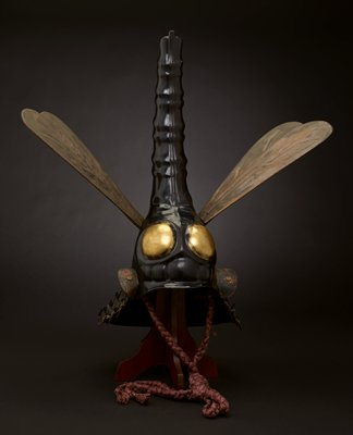 black and gold helmet in the form of a dragonfly, with its tail extending upward; two large gold eyes; two removable dull gold pairs of wings; thick braided purple silk cord tie at neck