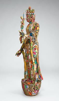slightly smaller than life-size sculpture of standing figure with elongated earlobes wearing a crown and garment with draping elements on sleeves and skirts, standing on a small rounded platform, holding a flower bouquet in PL hand; sculpture made up of small vertical pieces of corrugated cardboard with brightly-colored pigments on PL and PR faces; top of bouquet is removable; thin yellow ring at upper back of figure's interior