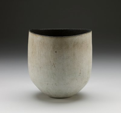off-white oval glazed ceramic vessel with hints of tan, grey, and beige; black lip and matte black interior; lip is slightly dipped to show contrasting black interior; exterior is relatively smooth with a few texture marks; dark interior is thoroughly textured