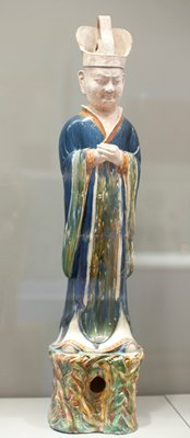 Dignitary. Military leader. Glazed pottery tomb figure, one of pair, mounted on a stand. The costume includes a blue robe, pleated brown skirt and white underskirt. Head and headdress unglazed.