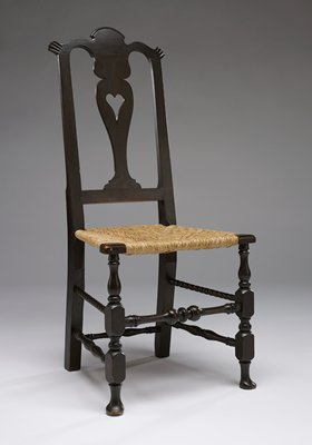 backrest has vase-like central element with heart cutout at center; two scalloped elements at top corners of backrest; three rounded lobes at top of backrest; straight back legs with square cross-sections; front legs are turned with pad-like feet; turned spindles--spindle at front has three large knobs at center, top spindles on sides have even beadlike patterning; woven plant fiber seat in trapezoidal shape