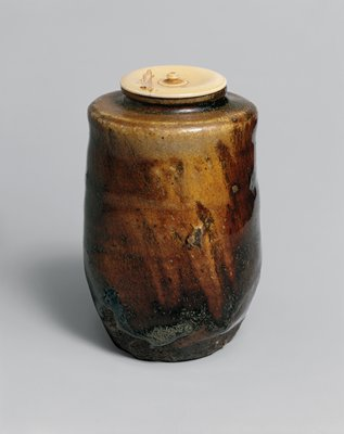 tea caddy, large, katatsuki shape, irregular surface; dark brown glaze, slightly flared shoulder, short neck; tapers subtly at base; ivory cover with tiny finial and incised concentric lines around finial
