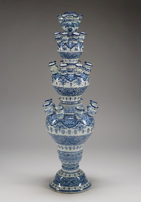 blue and white glazed Delftware vase divided into four sections that separate; each section baluster-shaped with openings at top that recede in size toward the top; small baluster-shaped spouts surround openings; overall design consists of alternating scroll patterns with ornamental woven florals; largest section on bottom with eight spouts in a circle around the opening; lower middle section smaller, with base meant to fit into opening of bottom section, and eight spouts surround top opening; upper middle section smaller has eight smaller spouts, hole in center; top section smallest in size, with six spouts surrounding vase opening; six leaf-shaped panels with various floral designs around middle center of top section