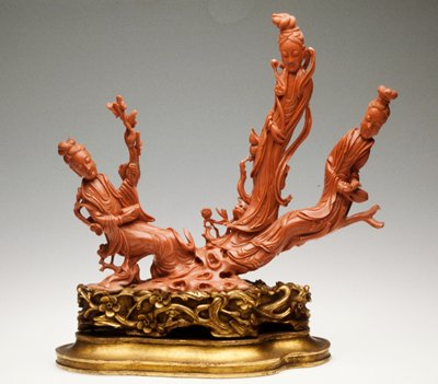 Three figure group of peach color coral, probably a representation of three different attitudes of the Daoist goddess Xiwangmu. Head of figure on right mended. Spray on left side mended.