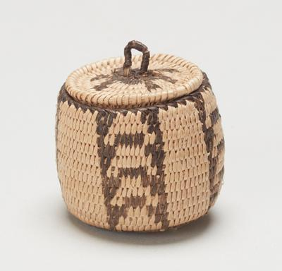 Miniature covered basket; coiled. Design consists of four panels of ladder-like motifs.  Motif on cover may be some kind of animal.  Colors are natural and black.