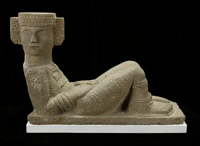 Sculpture determined to be a copy of a work from Chichen Itza, Yucatan Peninsula. Reclining figure resting on elbows, head turned sharply to right, legs drawn up and feet resting flat. The hands are placed on the thighs. Flat, cap-like headdress with elaborate ear ornaments carved only in front. Large pectoral, wristlets resembling three rows of fringe, anklets, thonged sandels. Right knee cap restored, lower neck restored, left hand restored, right hand cracked. The base is chipped near the left foot, and a piece is missing at the left corner below figure's shoulder. Authenticity in doubt: 1975.