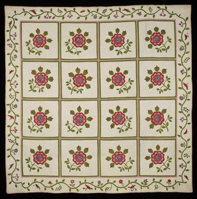 16 blocks of hand appliqued red flowers with printed centers and green leaves; borders are scrolling foliage with appliqued and embroidered birds and flowers; white backing
