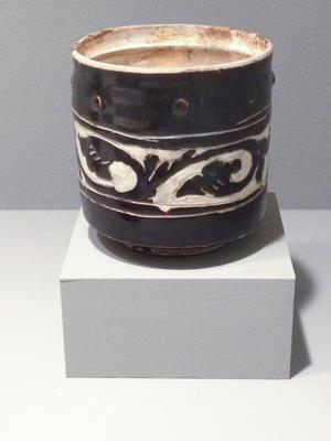 Tzu-Chou ware Bowl cylindrical, on ring foot; buff glazed interior and brown and white exterior with band of flowers and eight recessed dots above; stone ware