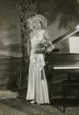 woman with flowers standing next to piano