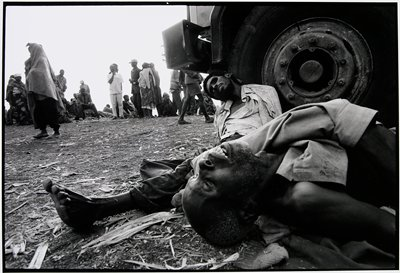 two dead men near wheel of truck one propped against it, the other laying on the ground; people are standing on a road nearby