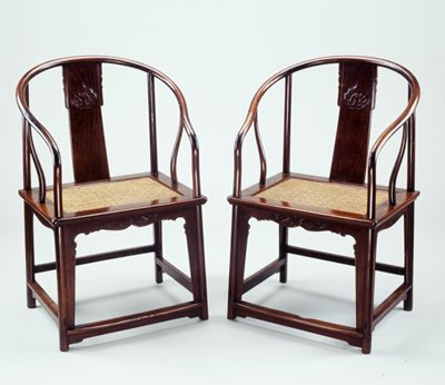 Chair with arms and upper back looped into horseshoe shape; central back panel has carved organic decorative elements; woven cane seat with diamond decorations