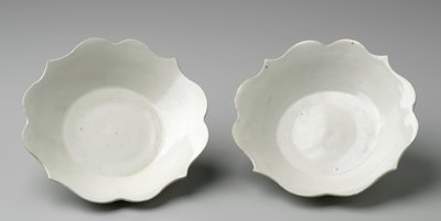 white dish on a medium-sized foot; edge cut with pattern of 2 scallops followed by a point