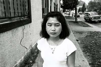 black and white photo of girl in white shirt, three white triangles on face
