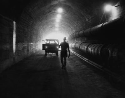 Black and white photograph of a man walking toward a vehicle in silhouette in a tunnel