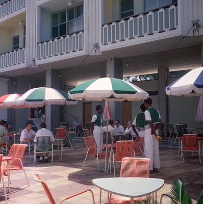 Color photograph of a patio with orange chairs and green and white umbrellas