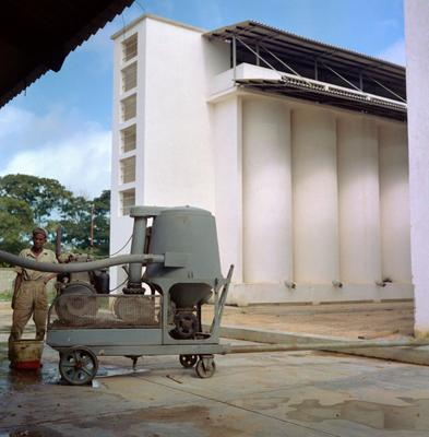 Color photograph of a figure operating a green machine in front of a white grain storage building