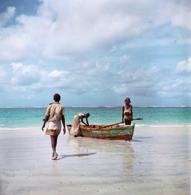Color image of three figures with a row boat on a beach