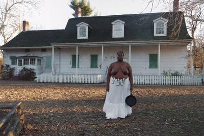 color image of a topless Black woman wearing a long white skirt with two pairs of baby shoes tied around her waist and holding a cast iron skillet in her PL hand; white Colonial-style house with green shutters behind woman