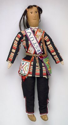 doll, cloth with leather moccasins, two beaded shoulder bags, one containing wood arrows in a quiver, doll has human hair.