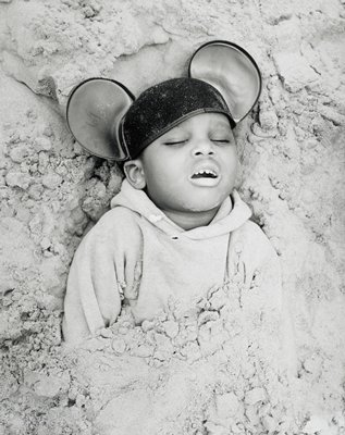 boy with eyes closed and mouth open; partially burried in sand