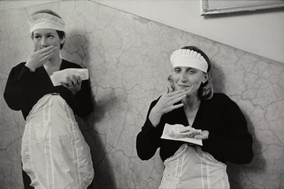 two women in maid uniforms leaning against marble wall, holding open-faced sandwiches; L woman has PR hand over mouth; R woman has PR hand up to chin