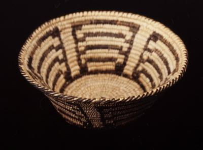 Miniature round basket; coiled. Design consists of a bands of human figures with joined hands. Colors are natural and black.