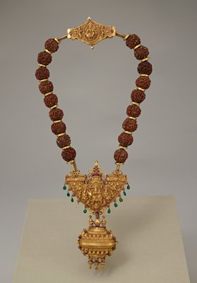pendant suspended from a garland of twin rudraksha berries; central gold piece depicting two figures on a bull; one emerald pendant at bottom split during installation, two pieces stored in envelope in A12.3 MS