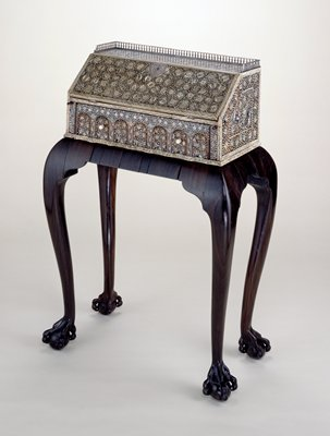 small writing desk having a circular floral pattern adorning the major surfaces (top, sides and front of door) with handles on either sides, hinges, top guard rail and front heart shaped lock plate of silver; ebony stand for cabinet said to be made in Portugese colony of Goa, India