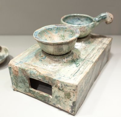 Stove, pottery, two holes; reddish-brick earthenware, lead glaze; one fitted with kettle, the other with a bowl; coated with a green mottled glaze, turned to silver iridescence through burial. Repaired. Stoves with accessories are extremely rare.