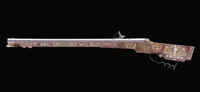 octagonal rifle barrel with simple decoration at the breech; wheel pierced by four hearts; trigger guard forged with three loops at cusps of finger grooves; bone and mother-of-pearl inlay throughout, cheek inlaid with a standing south American Indian. 