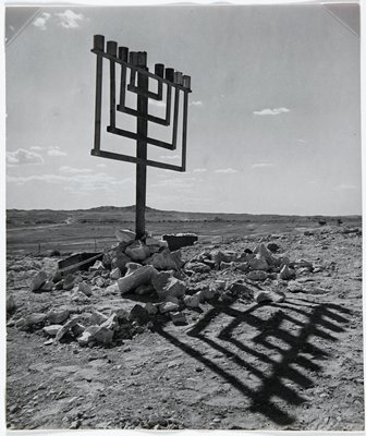 menorah with rocks piled around base outside