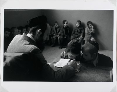 man showing two children a book, children in background along wall