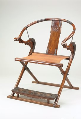 folding chair with woven seat; inlaid iron decorations on arms and footrest; carved open-mouthed animals where arms attach to seat