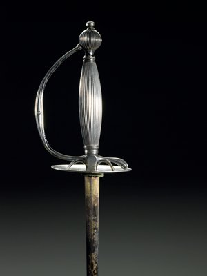 antique silver sword; linear decoration on handle; iridescent blue/purple stain at base of shaft with carved decoration.