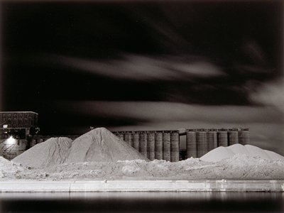 night scene with grain elevators behind 3 large piles of sand; building at left