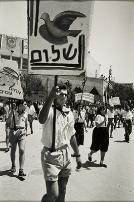 parade with young men in shorts and white shirts carrying signs and young women in dark skirts and white blouses carrying the hammer and sickle symbol on poles; matted
