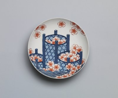 shallow dish on low foot; design of three blue cylindrical baskets with open weave, filled with robust red cherry blossoms; stylized waves at bottom; blue flowers with vines on underside and vertical painted ridges on foot