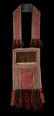 pouch and strap of finger-woven yarn in green and dark red with zigzag rows of white beads in fibers; beaded, tasseled and undecorated fringe at strap ends and bottom of bag; dark green pouch backing; blue and tan plaid backing on strap