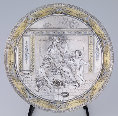 concave, plate-like shape; relief design of seated woman wearing a gauzy drape in an interior; putti with flowers wearing a necklace on PL side of woman; another figure places a basket of flowers at woman's feet